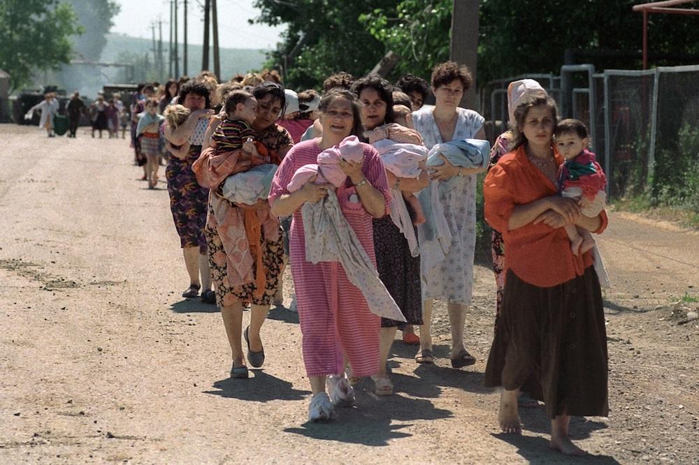 Освобожденные российские заложники, в основном женщины и дети, покидают в сопровождении военных больницу