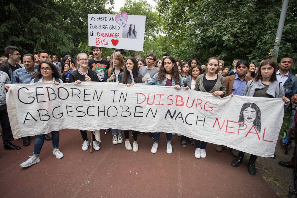 Протестующие 12 июня с плакатом «Рожденную в Дуйсбурге депортировали в Непал»