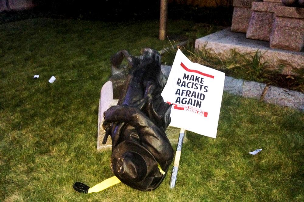 Транспарант с надписью «Заставьте расистов снова бояться» рядом со снесенным памятником