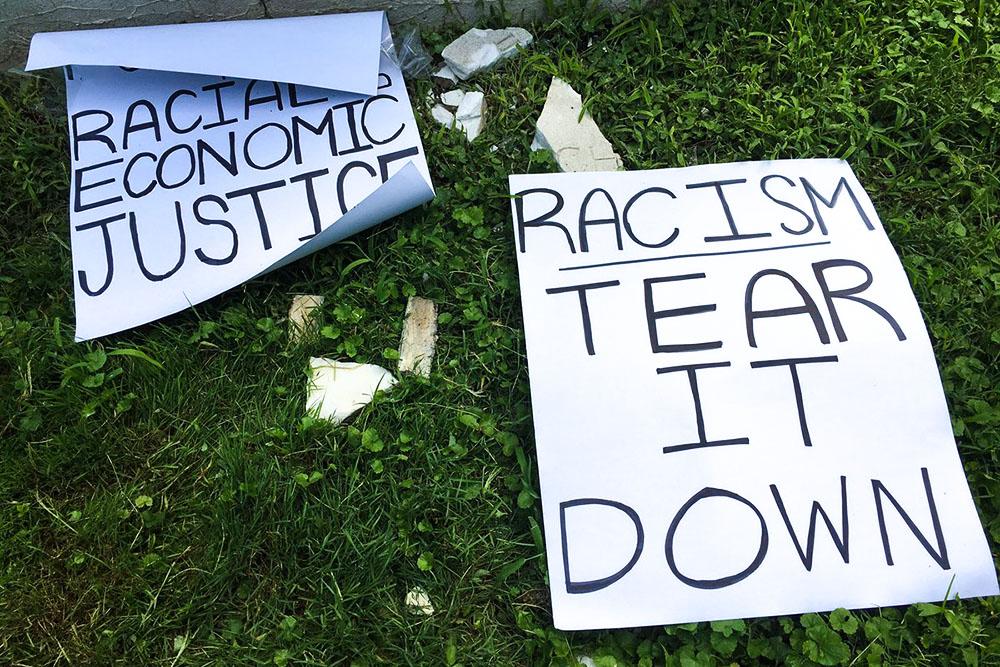 Плакаты «Будущее — это расовая и экономическая независимость» и «Снести расизм» рядом с памятником