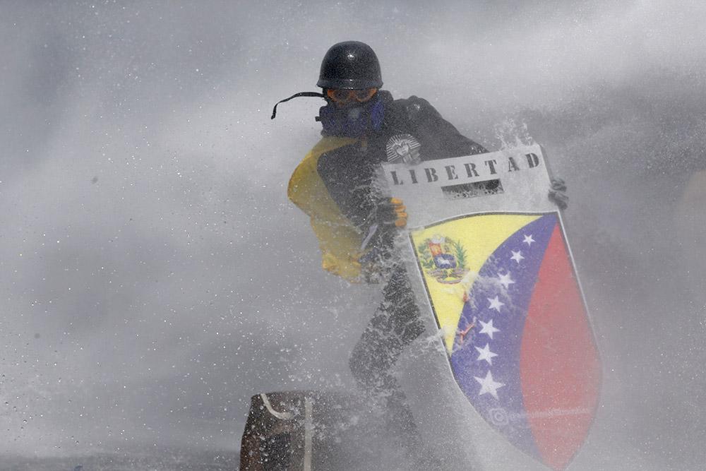 5 октября, Каракас. Участник акции против политики президента Венесуэлы Николаса Мадуро прикрывается от струи воды щитом, на котором написано «Свобода»