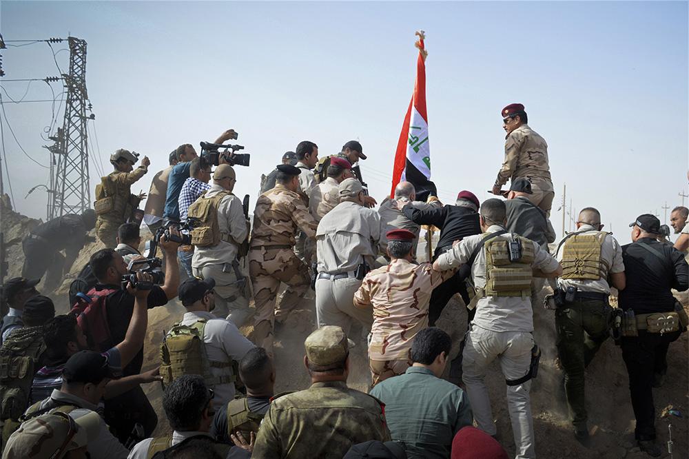 5 ноября. Премьер-министр Ирака Хайдер Аль-Абади поднимает национальный флаг в окрестностях города Эль-Кайма, освобожденного от боевиков ИГИЛ (организация запрещена в России)