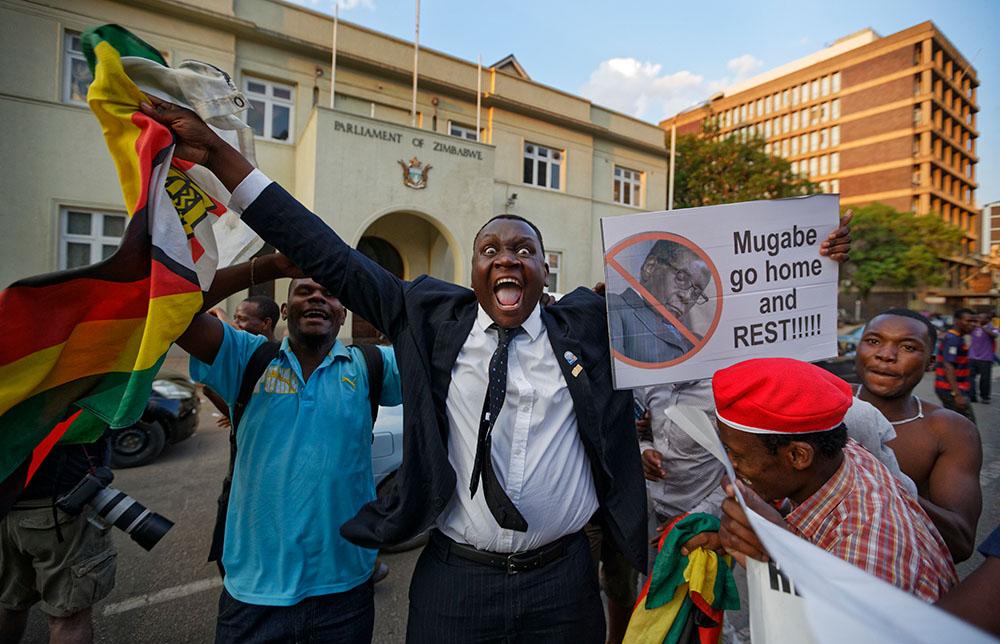 21 ноября, Хараре. Жители Зимбабве у здания парламента страны радуются новости об отставке президента Роберта Мугабе