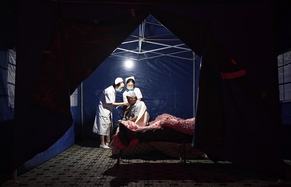 9 августа, Сычуань. Мединский персонал осматривает пострадавшего во время землетрясения мужчину