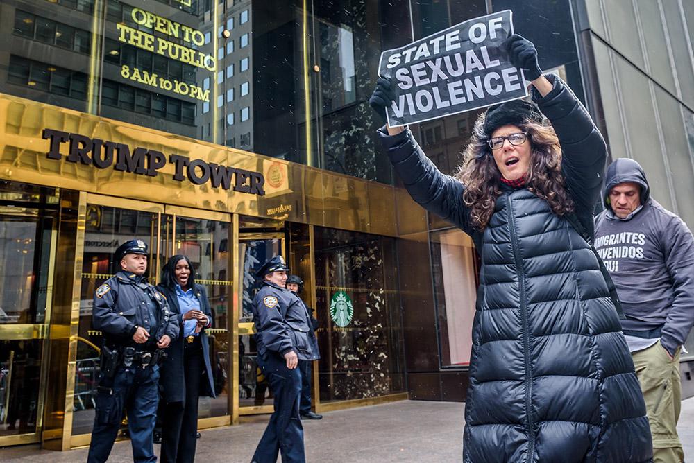 Женщина протестует против политики Дональда Трампа около его небоскреба в Нью-Йорке